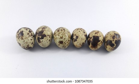 Close-up view of raw quail eggs on a white background.