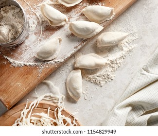 Close-up view of raw russian dumplings with flour on table. Cooking background