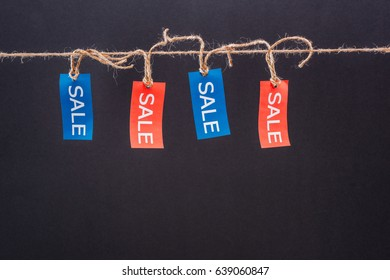 Close-up view of red and blue sale tags hanging on rope isolated on black, Offer sale tags