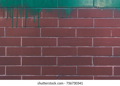 close-up view of red brick wall with stains of green paint texture