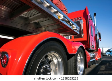 Close-up view of red classic bonnet American big rig semi truck tractor with awesome stylish chrome accessories standing on truck stop with flat bed semi trailer caring covered commercial cargo