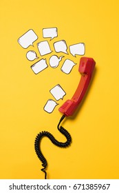 Close-up view of red telephone handset and blank speech bubbles isolated on yellow