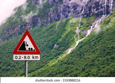 Closeup view of road sign falling stones, Traffic sign caution, possible falling rocks from the mountains. Beautiful waterfall and mountains as blurred background.