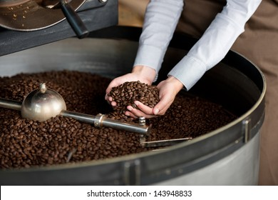 close-up view of roasted coffee beans in woman's hand