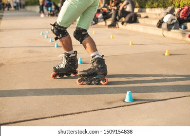 Close-up view of the rollers of a caucasian man, doing rollerblading, inline skating, performing on a slalom course on asphalt surface. Small cones for training on the road.