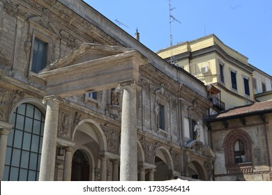 Close-up view to Roman style water well upper part of XVI century at the Mercanti square of Milan and Scuole Palatine facade in background.