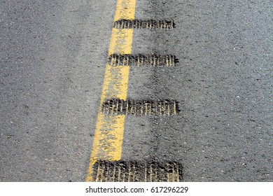 Closeup view of rumble strips on a road.
