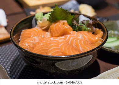 Closeup view of salmon don, Japanese salmon dish made from raw salmon slices on top of rice with ginger as side dish. Concept of healthy diet with omega 3 from fish oil. Selective focus on fish