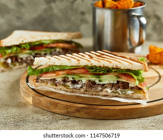 Close-up view of sandwich with beef, tomatoes and cucumber. Crispy fried potato on background