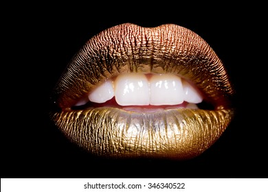 Closeup view of sexual beautiful female open golden lips with white teeth isolated on black background, horizontal picture