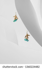 Closeup view shot of two dangle earrings with pendants in view of sand swallow. There are turquoise stones as additional pendants. The set is isolated on relief platform, located on white background.