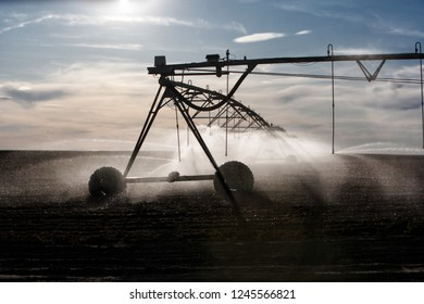 A closeup view of the silhouetteof a high tech agricultural sprinkler watering farm crops.