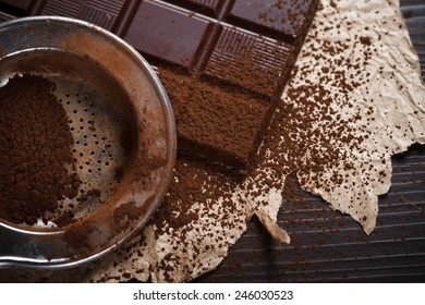 Closeup view of silver sieve with cocoa powder and chocolate bar, retro style