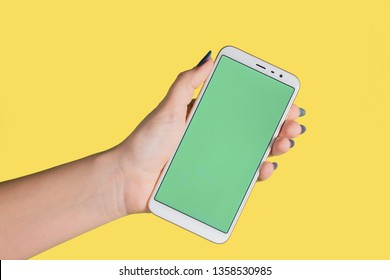 Closeup view of single female caucasian hand holding modern mobile smartphone with empty green screen isolated on bright yellow background. Horizontal color photography.