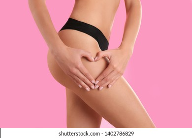 Closeup view of slim woman in underwear making heart with hands near thigh on color background. Cellulite problem concept