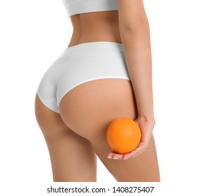 Closeup view of slim woman in underwear with orange on white background. Cellulite problem concept