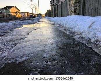 A closeup view of slippery black ice covering a sidewalk in the early morning of a residential neighbourhood during the winter in Edmonton, Alberta, Canada.