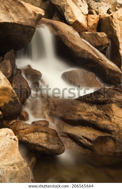 Close-up view of soft flowing small waterfall surrounded by golden brown rocks
