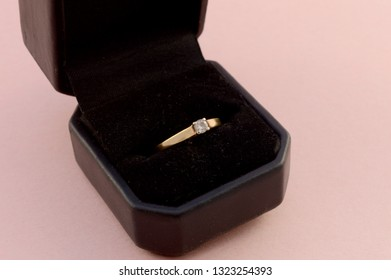 Closeup view of a solitaire diamond ring set in yellow gold inside a display case.