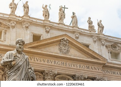 Closeup view of the St. Peter Statue. St. Peter's Basilica is in the background.
