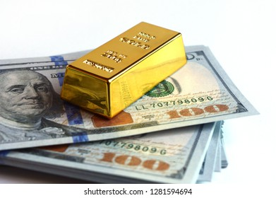 Closeup view of a stack of hundred dollar american bills with a fine gold ingot resting on top.