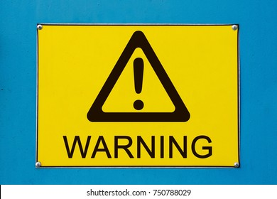 Closeup view of street warning exclamation sign on yellow metallic board