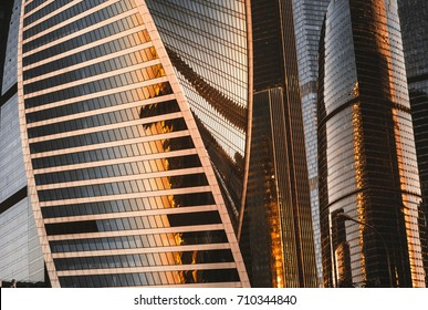 Close-up view of super modern glassy facades of Moscow City skyscraper group reflecting sunset of metropolis by thousands of windows; irregular, striped and bent structure, autumn evening, Russia
