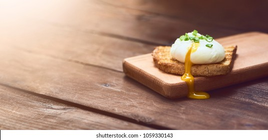 Close-up view of a Tasty poached egg with liquid yolk with fresh basil leaves on toast on cutting board over dark brown rustic wooden background