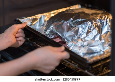 closeup view teen hands putting raw beef cross rib chunk covered with cooking foil on tray into the oven