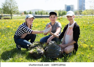 Close-up view of teenagers with gloves and garbage bags walking. Ecology protection concept.