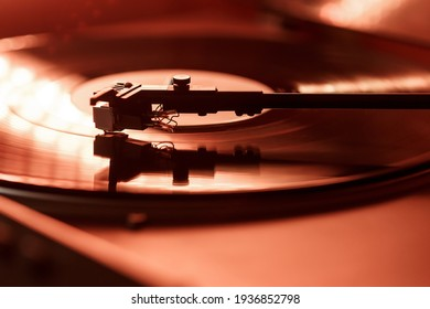 Closeup view of a tonearm and turntable playing vinyl record. Entertainment and music trends