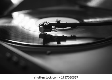 Closeup view of a tonearm and turntable playing vinyl record. Entertainment and music trends. Black and white image