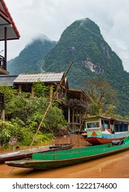 Closeup View of Traditional Fishing Skiff Floating Next to Small Village with View of Mountain Crag Peaks in Distance. Rain Forest Setting. (Muang Ngoi, Nam Ou River, Laos).