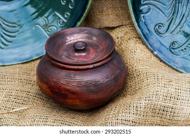 Close-up view of traditional old clay pot and blue plates with ornament on sackcloth