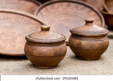 Close-up view of traditional old clay pots and plates with ornament on sackcloth