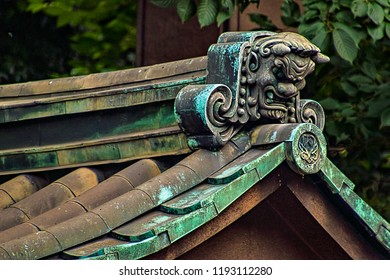 Closeup View of Traditional Oni Ogre Face on Temple Rooftop (Tokyo, Japan).