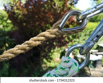 Closeup view of a traditional rope with splice and thimble and a modern rope with knot and metal ring. Trees in the blurred background
