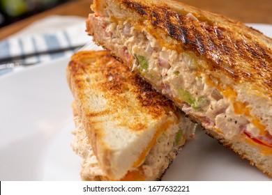 A closeup view of a tuna melt sandwich, in a restaurant or kitchen setting.
