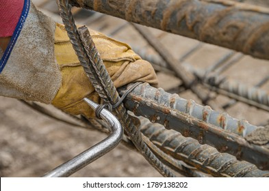 Close-up view of the twisting of steel wires over construction rebar rods Assembling construction iron rods to make columns and beams
