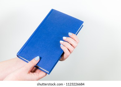 Closeup view of two female hands holding blue paper book isolated on white background. Horizontal color photography.
