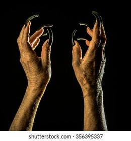 Closeup view of two female old scary mystic hands with long black nails on fingers of witch zomby demon or devil on halloween holiday character in studio indoor on dark background, square picture