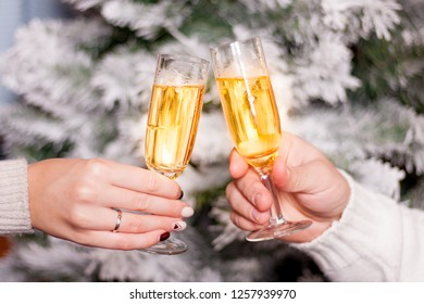 Closeup view of two hands with wine glasses with wine or champagne. Love and romance couple celebrate xmas or New year holiday.