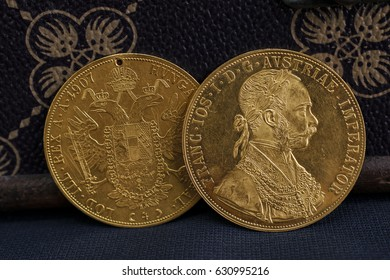 Close-up view of two on one another Austria-Hungary thalers, avers and revers of golden coin-ducats from 1915 with Kaiser Franz Joseph I, leaning on treasure chest and dark environment
