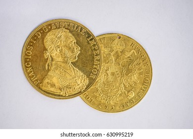 Close-up view of two on one another Austria-Hungary thalers, avers and revers of golden coin-ducats from 1915 with Kaiser Franz Joseph I, on white background