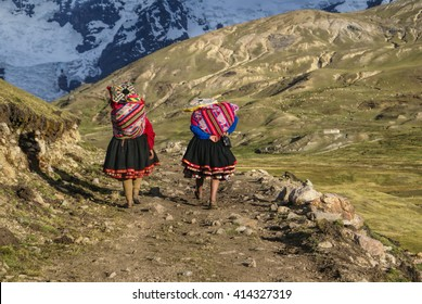 Close-up view of two Peruvian woman walking along the path in Peruvian Andes