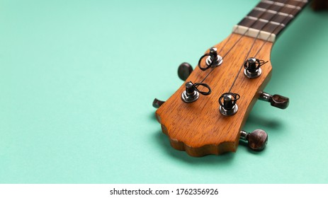 Closeup view of ukulele headstock. Cyan background copy space.