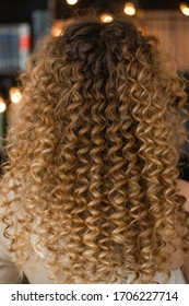 Closeup view vertical photography of amazing beautiful long curly female hair style made in professional beauty spa salon.