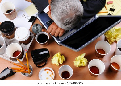 Closeup view of a very cluttered and stressed out businessman's desk. Overhead view of the mature man's head on laptop keyboard and scattered coffee cups and office supplies. Horizontal format.