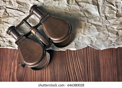 Close-up view of a vintage binoculars and an old paper sheet on wooden background