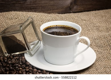 Closeup view of the vintage photo of the white cup of coffee standing on the sackcloth. Around it are scattered coffee beans and ground coffee glass
